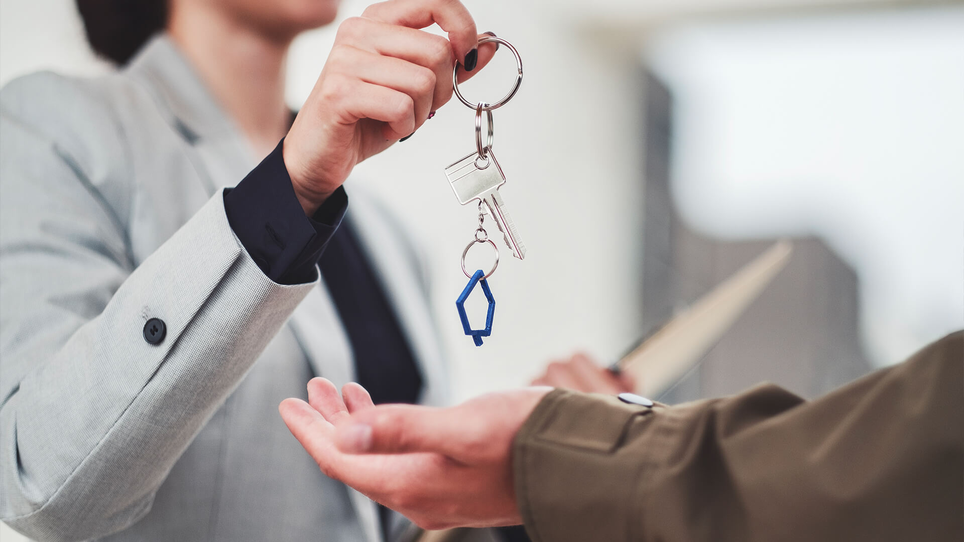 Realtor handing keys to new homeowner