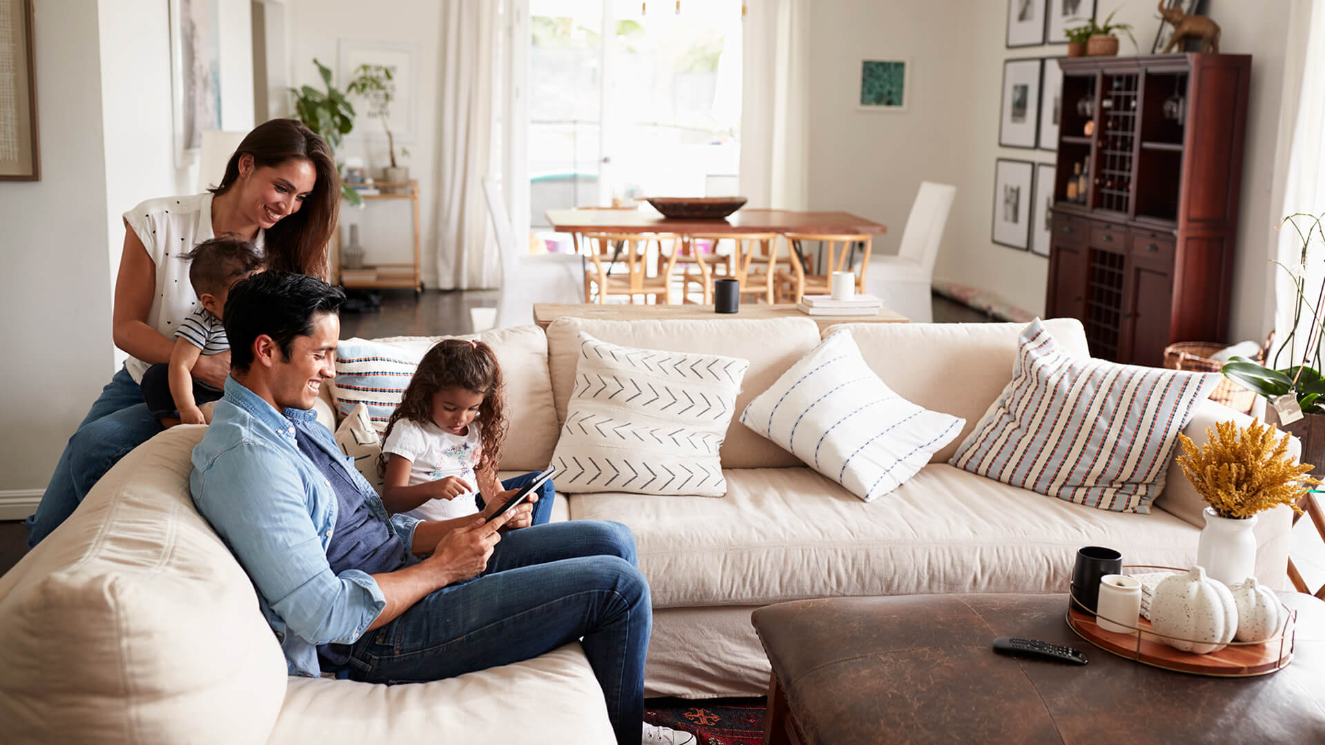 Smiling family gathered around a tablet in new home