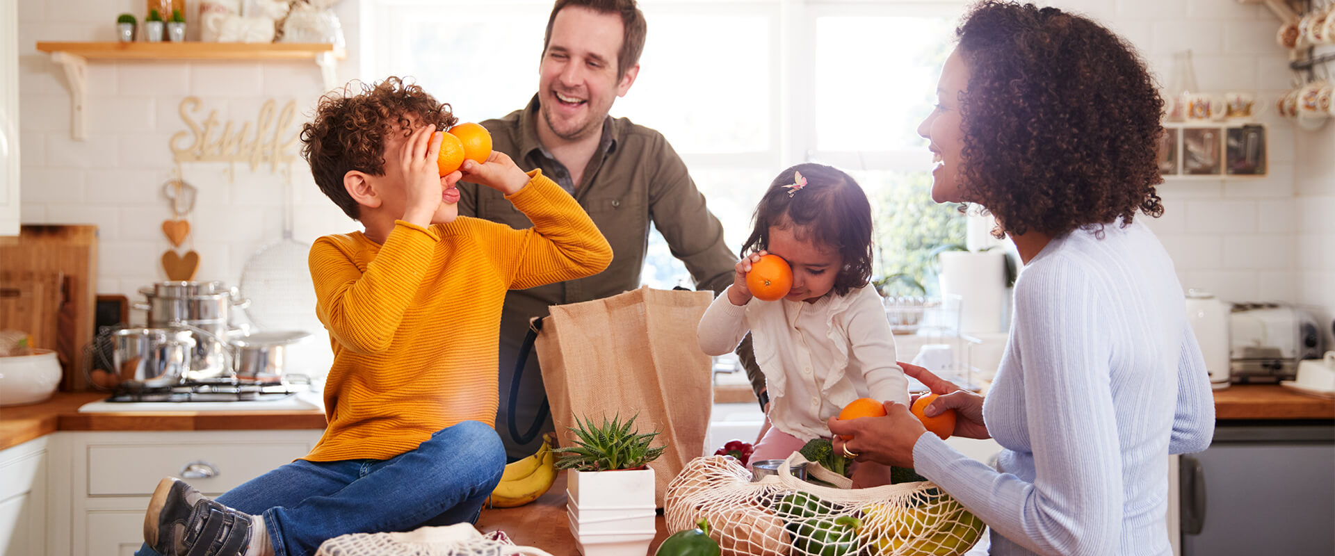 family laughing with groceries in the kitchen
