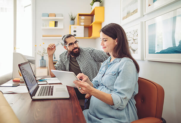 Couple using tablet and laptop for planning finances